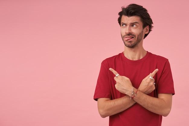 Retrato de jovem com corte de cabelo da moda apontando com os dedos indicadores em diferentes direções, em pé na rosa em uma camiseta vermelha, olhando para o lado e mostrando a língua
