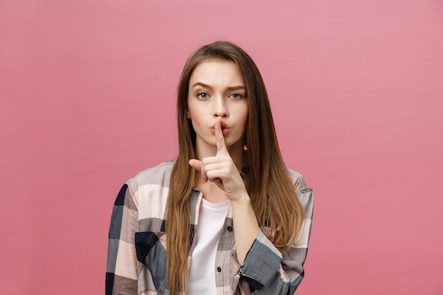 Retrato de jovem com dedo nos lábios contra parede rosa