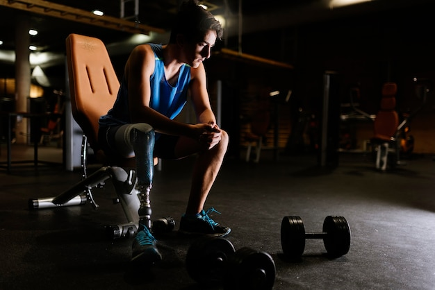 Retrato de jovem com deficiência no ginásio. conceito de desportista com deficiência.