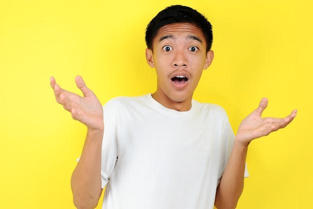 Retrato de jovem com expressão facial chocada, isolado no amarelo