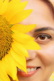 Retrato de jovem com flor de girassol, close-up, temporada de verão