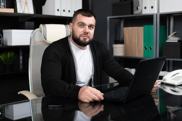 Retrato de jovem com laptop no escritório de negócios