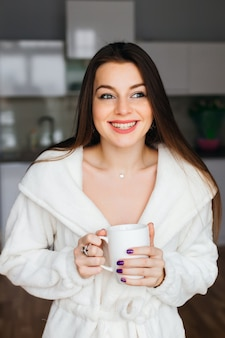 Retrato de jovem com manto branco após o banho segura uma xícara com café ou chá no contexto da cozinha. feche o sorriso dentuço do rosto.