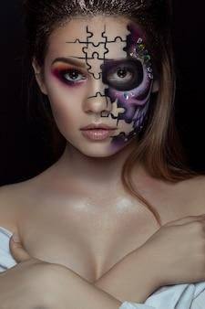 Retrato de jovem com maquiagem de halloween com medo sobre preto
