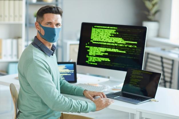 Retrato de jovem com máscara protetora, olhando para frente enquanto escreve códigos no escritório de ti