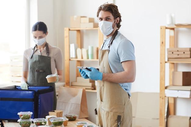 Retrato de jovem com máscara protetora usando o tablet pc no trabalho enquanto trabalhava no serviço de entrega com seu colega ao fundo