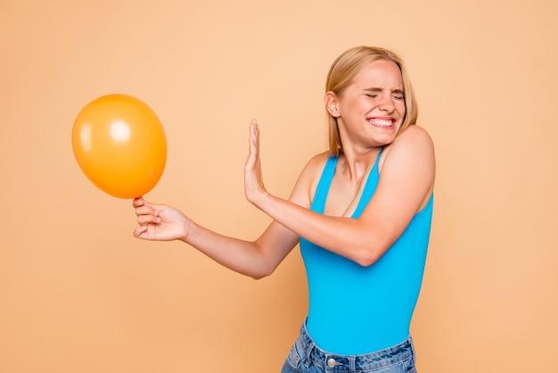 Retrato de jovem com medo de balão de ar hélio isolado em bege