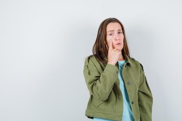 Retrato de jovem com o dedo na bochecha em camiseta, jaqueta e olhando a vista frontal ofendida