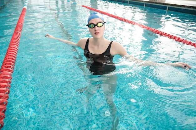 Retrato de jovem com óculos de natação e boné relaxando na piscina