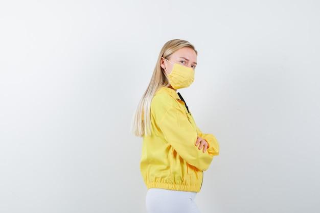 Retrato de jovem com os braços cruzados na jaqueta, calça, máscara e parecendo triste