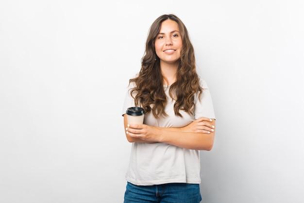Retrato de jovem com os braços cruzados segurando uma xícara de café para ir