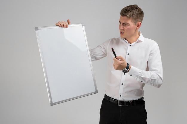 Retrato de jovem com placa magnética limpa e marcador nas mãos dele isolado no fundo branco