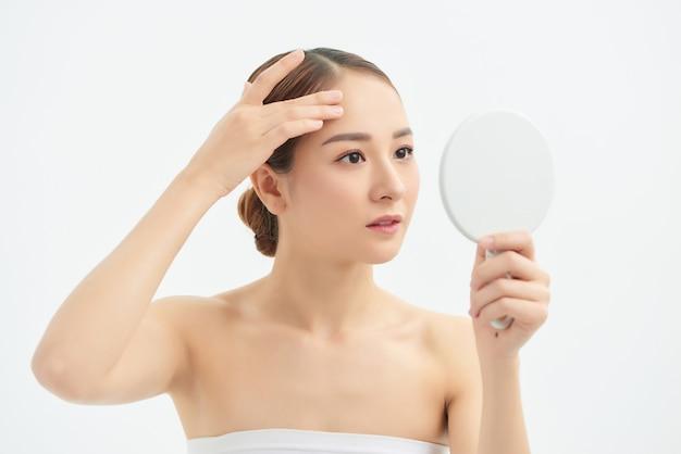 Retrato de jovem com problema de acne, olhando no espelho em fundo branco