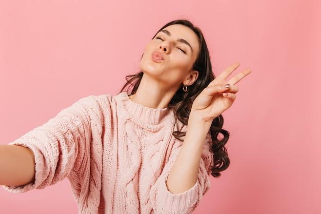 Retrato de jovem com roupa de malha, tomando selfie no estúdio rosa. senhora de olhos fechados manda beijo no ar e mostra o símbolo da paz.