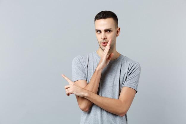 Retrato de jovem com roupas casuais sussurrando um segredo por trás da mão, apontando o dedo indicador para o lado