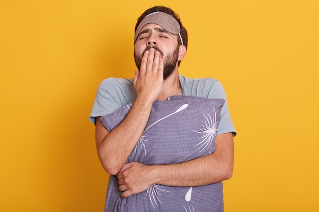 Retrato de jovem com sono com o travesseiro nas mãos, bocejando e cobrindo a boca com as palmas das mãos, posando com venda na testa