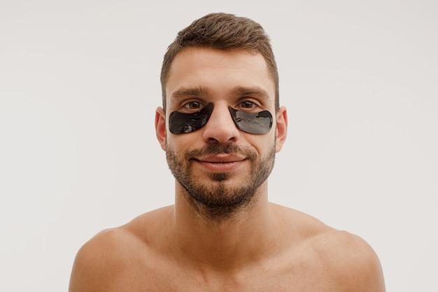 Retrato de jovem com tapa-olho no rosto. sorridente barbudo europeu com a pele perfeita, olhando para a câmera. conceito de cuidados com a pele do rosto. isolado em um fundo branco. sessão de estúdio. copie o espaço