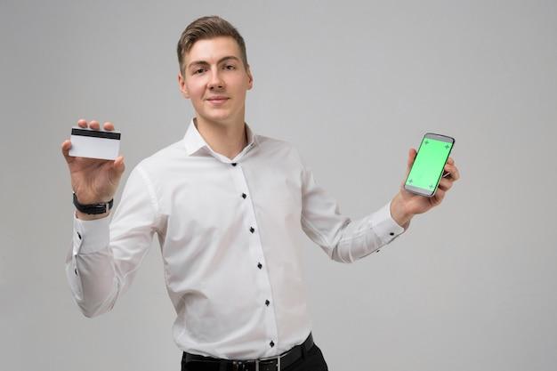 Retrato de jovem com telefone celular e cartão bancário nas mãos dele isolado no fundo branco