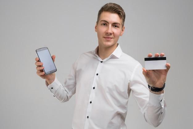 Retrato de jovem com telefone celular e cartão bancário nas mãos em branco