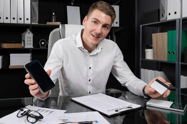 Retrato de jovem com telefone celular e cartão bancário, sentado à mesa no escritório brilhante