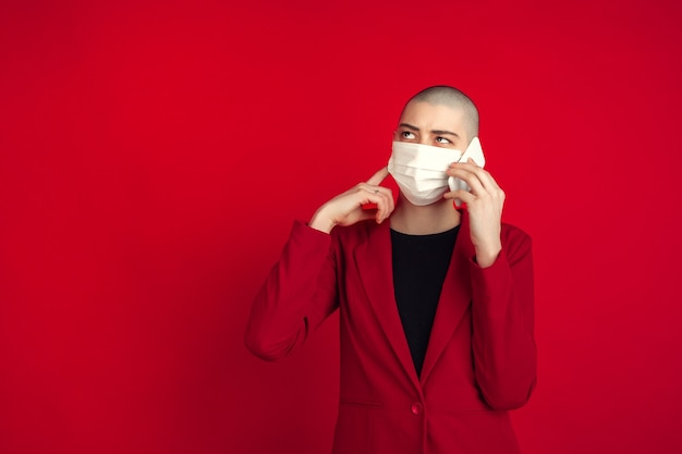 Retrato de jovem com terno vermelho e máscara branca falando ao telefone isolado no estúdio vermelho