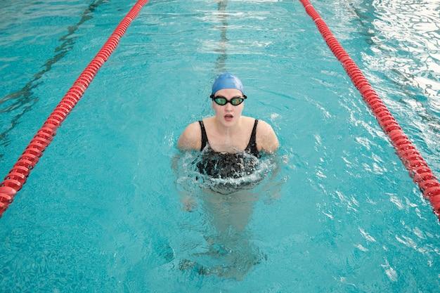 Retrato de jovem com touca e óculos de proteção deslizando para fora da água na piscina