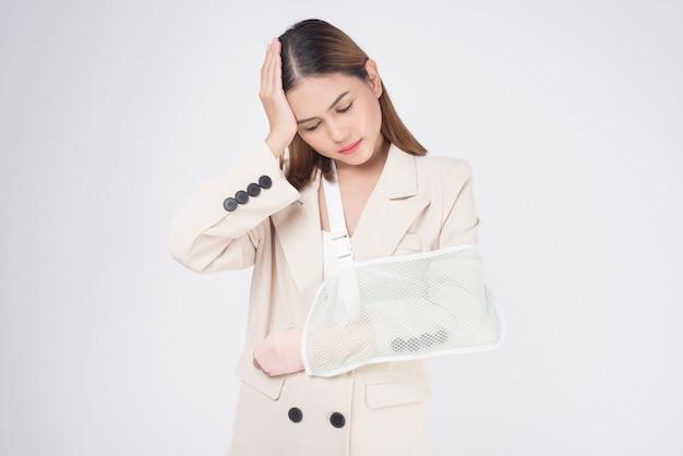 Retrato de jovem com um braço ferido na tipóia sobre fundo branco em estúdio.