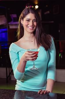 Retrato de jovem com um cocktail no bar balcão em bar