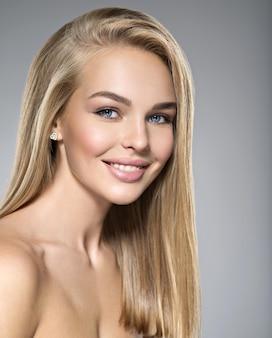 Retrato de jovem com um lindo sorriso. menina muito linda com cabelos lisos longos e claros e maquiagem marrom. rosto de olhos azuis de um modelo de moda. posando