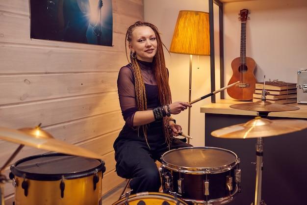 Retrato de jovem com um penteado estiloso, sorrindo para a câmera enquanto aprende a tocar bateria no estúdio
