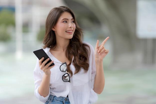 Retrato de jovem com uma carinha sorridente, usando um telefone, caminha por uma cidade