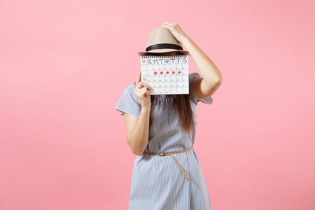 Retrato de jovem com vestido azul, chapéu segurando o calendário de períodos para verificar os dias de menstruação, isolados em um fundo rosa tendência brilhante. conceito médico, de saúde e ginecológico. copie o espaço.