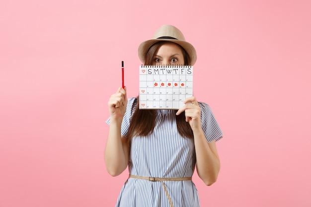 Retrato de jovem com vestido azul, chapéu segurando um lápis vermelho, calendário de períodos femininos para verificar os dias de menstruação isolados no fundo rosa. saúde médica, conceito ginecológico. copie o espaço