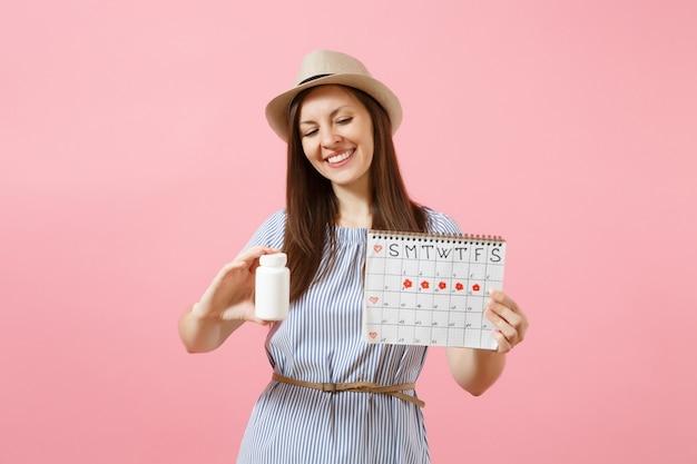 Retrato de jovem com vestido azul, segurando o frasco branco com comprimidos, calendário de períodos femininos, verificando os dias de menstruação isolados no fundo. conceito ginecológico de saúde médica. copie o espaço.