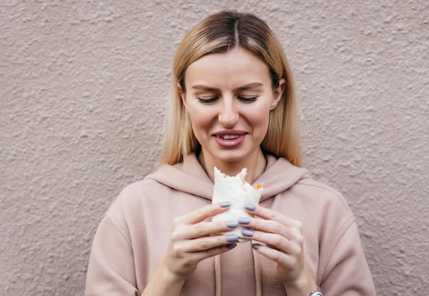 Retrato de jovem comendo frango enrolado na rua