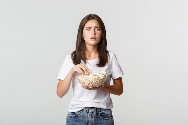 Retrato de jovem compassivo, assistindo a um filme comovente, comendo pipoca.