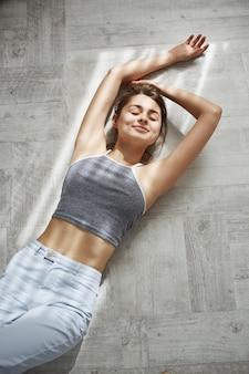 Retrato de jovem concurso mulher bonita com os olhos fechados, sorrindo, deitado no chão na luz solar da manhã.