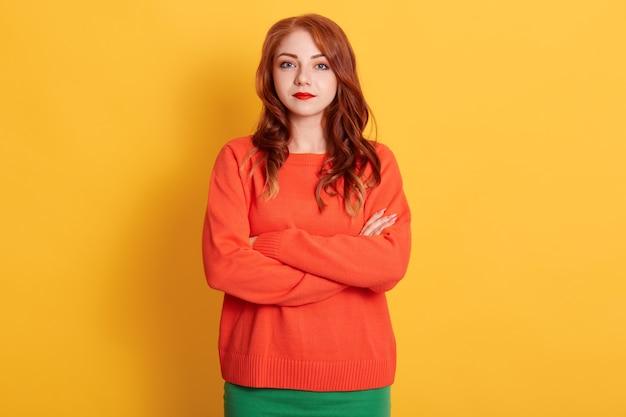 Retrato de jovem concurso mulher europeia de cabelos vermelhos com olhar sério, vestindo um suéter laranja, olhando para a câmera com uma expressão calma ou triste