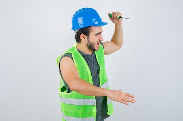 Retrato de jovem construtor levantando a mão para atacar com uma chave de fenda de uniforme e olhando a vista frontal louca