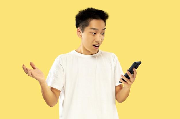 Retrato de jovem coreano. modelo masculino em camisa branca. usando smartphone para apostas, leitura de notícias ou conversas. conceito de emoções humanas, expressão facial.