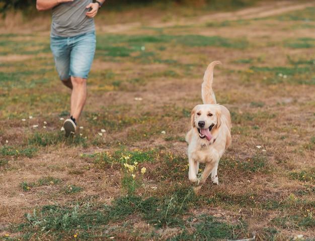 Retrato de jovem correndo com cachorro retriever dourado.