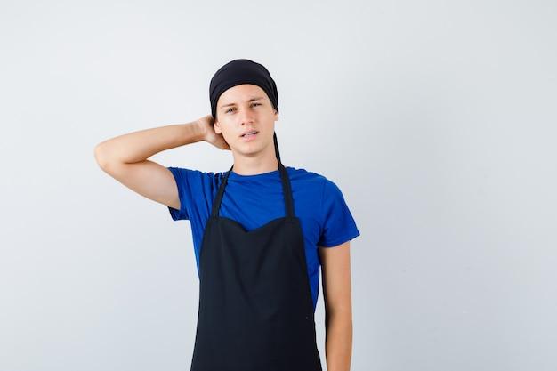 Retrato de jovem cozinheiro adolescente com a mão atrás da cabeça em t-shirt, avental e olhando pensativamente vista frontal