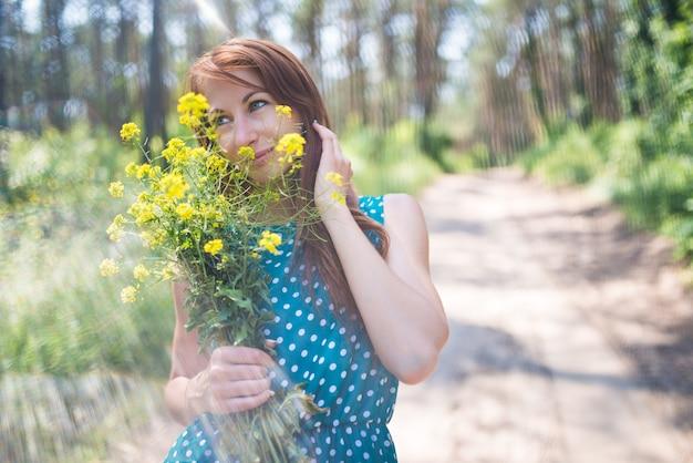 Retrato de jovem de olhos verdes segurando flores amarelas