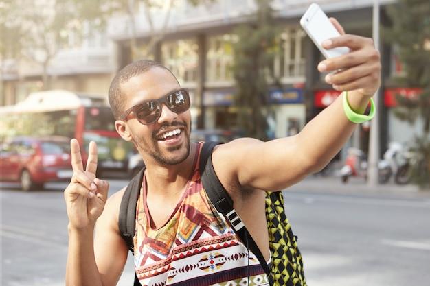 Retrato de jovem de pele escura feliz em óculos escuros e camiseta sorrindo enquanto toma selfie posando com gesto de paz