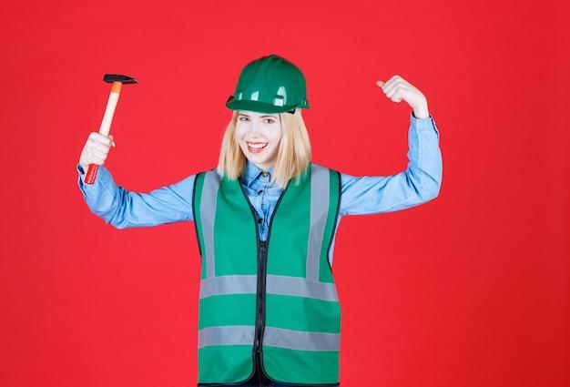 Retrato de jovem de uniforme e capacete levanta o braço para mostrar os músculos enquanto segura um martelo