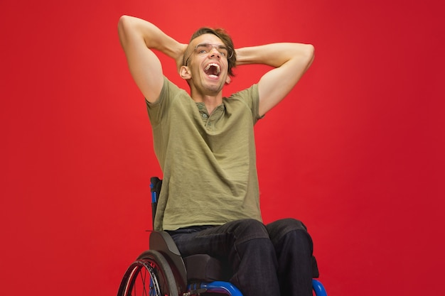 Retrato de jovem deficiente caucasiano isolado no fundo vermelho do estúdio.