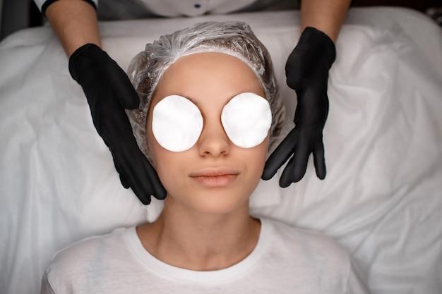 Retrato de jovem deitado no sofá. ela tem esponjas brancas nos olhos. as mãos de esteticista em luvas pretas tocam a pele do rosto.
