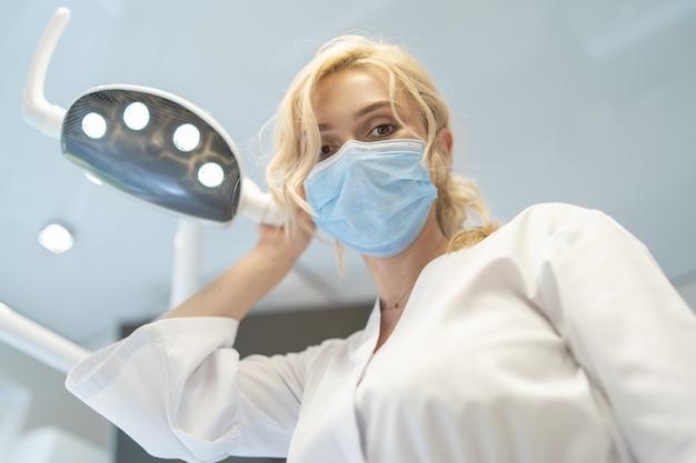 Retrato de jovem dentista feminino sorridente em consultório odontológico moderno.