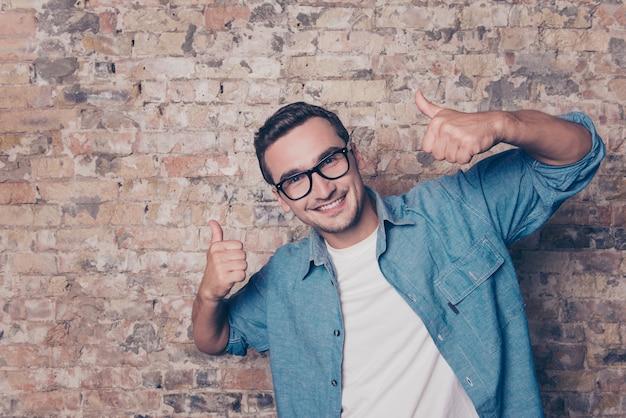 Retrato de jovem dentuço mostrando os polegares