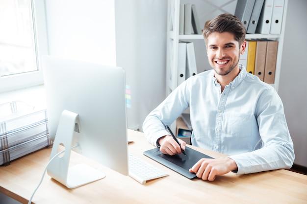 Retrato de jovem designer sorridente, trabalhando e usando tablet gráfico no escritório